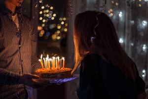 אישה מביעה משאלה ומכבה נרות על עוגת יומולדת