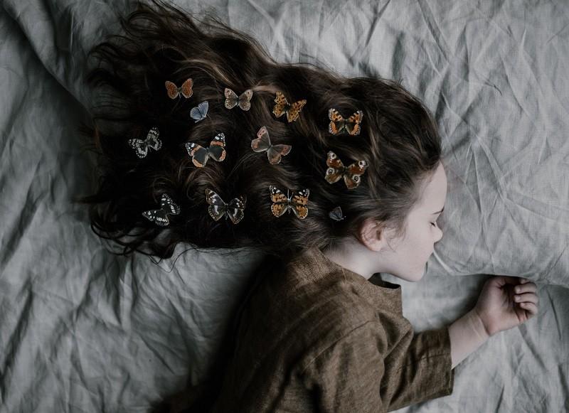 ללכת לישון מוקדם ובשמחה: בחורה צעירה ישנה עם פרפרים בשיער