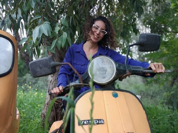 מיכל פולת משתעשעת ברכיבה על קטנוע ווספה ביער