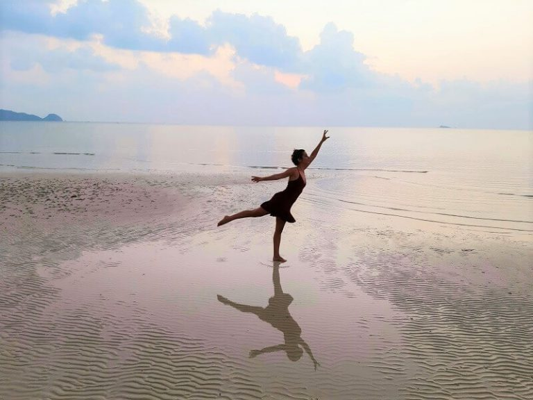 מיכל פולת בתנוחת ריקוד על החוף בקופנגן שמייצגת מעבר בין העולם הישן לעולם החדש