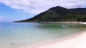 חוף בקופנגן עם מי טורקיז והר ג'ונגל ברקע