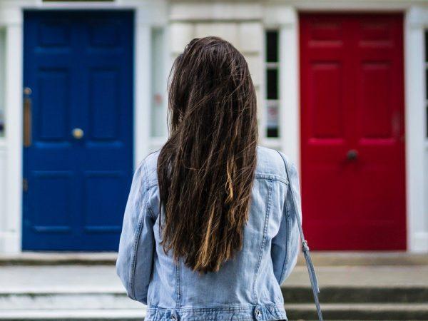 אישה עומדת בפני בחירה: דלת אדומה או כחולה
