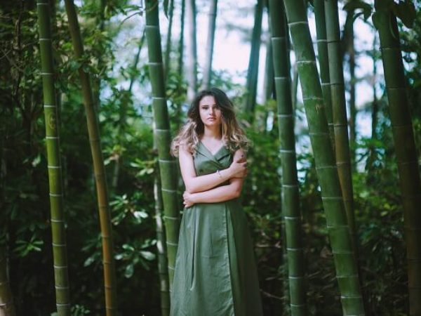 woman standing and hugging herself between bamboo trees